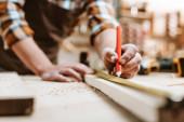 ořezaný pohled na muže držícího tužku u dřevěného prkna a měřicí pásku