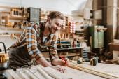 Selektiver Fokus eines glücklichen Holzarbeiters, der Bleistift in der Nähe von Holzplanke und Maßband hält