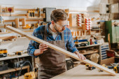 handsome carpenter in goggles holding wooden plank