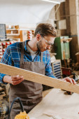 selective focus of handsome carpenter in goggles holding wooden plank in workshop
