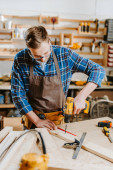 selective focus of carpenter in goggles and apron holding hammer drill