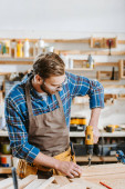 selective focus of woodworker in safety glasses and apron holding hammer drill near wooden planks