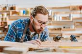 selektiver Fokus des Tischlers mit Schutzbrille, der Hammerbohrer in der Hand hält und auf Sägemehl in der Nähe von Holzplanken bläst