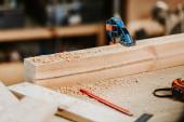 selektivní zaměření pilin na dřevěnou desku v blízkosti měřicí pásky