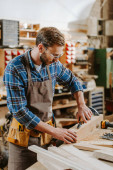 selective focus of carpenter in goggles holding pliers near wooden dowel