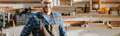 panoramic shot of cheerful carpenter in apron looking at camera in workshop