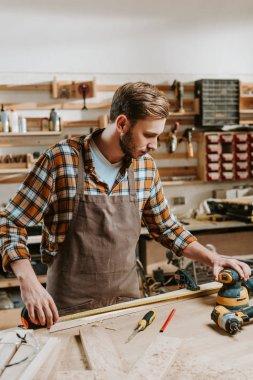 handsome carpenter in brown apron measuring wooden plank