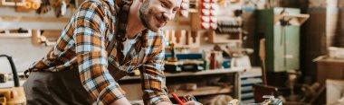 Panoramic shot of happy woodworker in workshop stock vector