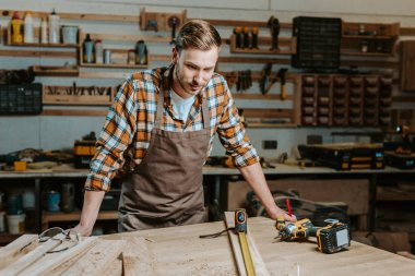 handsome woodworker looking at table with wooden planks and measuring tape