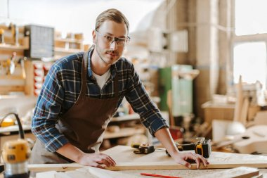 selective focus of handsome carpenter in goggles standing near wooden plank on table