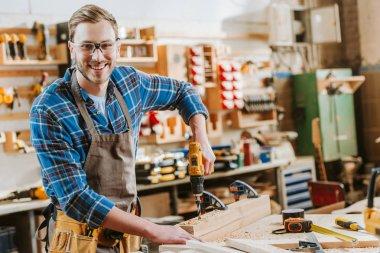 Gözlüklü ve önlüklü mutlu ahşap işçisi tahta kalasların yanında çekiç matkabı tutuyor.