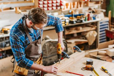 woodworker in goggles and apron holding hammer drill near wooden planks