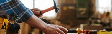 panoramic shot of carpenter holding hammer in workshop