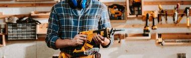 Panoramic shot of carpenter holding hammer drill stock vector
