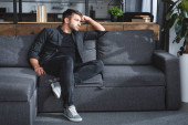 handsome and pensive man sitting on sofa in apartment
