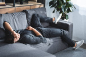 Fotografie high angle view of man with headache lying on sofa in apartment