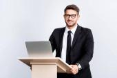 usmívající se obchodník v obleku stojící na pódiu tribuna během konference izolované na bílém