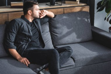 handsome and pensive man sitting on sofa and looking away in apartment