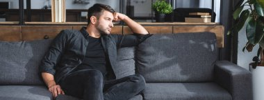 panoramic shot of handsome and pensive man sitting on sofa in apartment