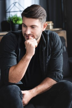 handsome and frustrated man with panic attack siting on sofa in apartment