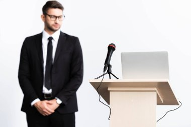 selective focus of podium tribune with laptop and microphone, businessman in suit on background isolated on white