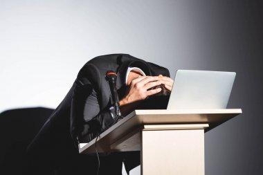 scared businessman in suit standing at podium tribune and hiding behind laptop during conference on white background