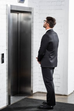 businessman in formal wear waiting for elevator in office