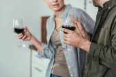 Cropped view of couple with wine glasses talking on kitchen