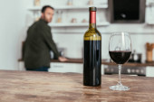 Selective focus of wine glass with bottle on table and man on kitchen
