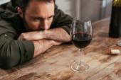 Selektivní soustředění zamyšleného muže hledícího na sklenici vína na stole