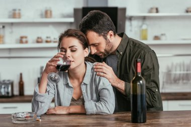 Upset man hugging alcohol addicted wife with wine glass at kitchen