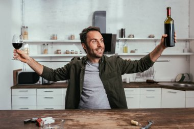 Exited man with wine glass and bottle beside cigarettes on kitchen table