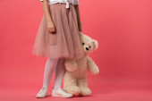 Photo cropped view of woman holding teddy bear on pink background