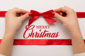 cropped view of woman touching red bow near merry christmas lettering on white