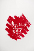 top view of red drawn stroke with my heart is wherever you are letters isolated on white
