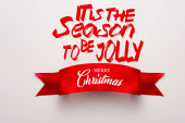 top view of red ribbon with its the season to be jolly, merry christmas lettering on white