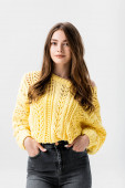 positive girl in yellow sweater standing with hands in pockets and looking at camera isolated on grey