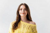 attractive girl in yellow sweater smiling at camera isolated on grey