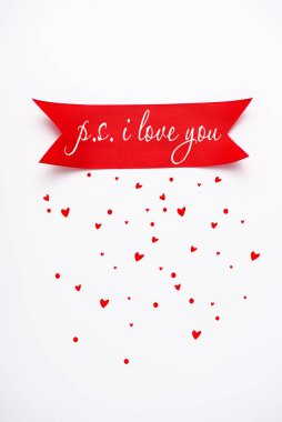 Top view of red satin ribbon with p.s. i love you letters near falling hearts on white stock vector