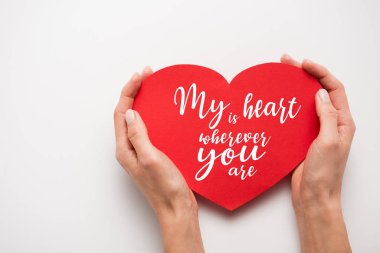 Cropped view of woman holding red heart shape paper cut with my heart is wherever you are letters on white stock vector
