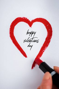 Cropped view of woman drawing heart with red lipstick near happy valentines day letters on white stock vector