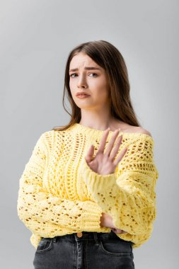 displeased girl in yellow sweater showing refusal gesture and looking at camera isolated on grey