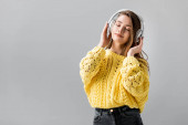 smiling girl dancing while listening music in wireless headphones with closed eyes isolated on grey