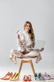 Fotografie cheerful girl holding laptop and credit card while sitting on chair in lotus pose near collection of shoes on grey background