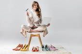 Fotografie cheerful girl sitting on chair in lotus pose, holding laptop and credit card near collection of shoes on grey background