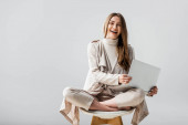Fotografie cheerful girl looking at camera while sitting on chair in lotus pose and holding laptop isolated on grey