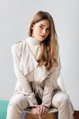 Fotografie attraktives, stylisches Mädchen, das in die Kamera schaut, während es isoliert auf einem Stuhl auf grau sitzt