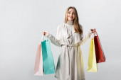 cheerful, stylish girl looking at camera while holding shopping bags isolated on grey