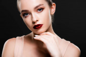 attractive young woman with bright red lips looking at camera isolated on black