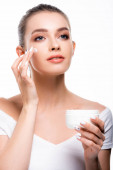 beautiful, smiling woman applying cosmetic cream on face and looking away isolated on white